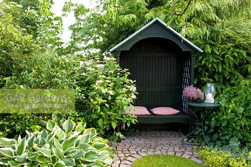 Wooden Arbour In Small Country Garden. Borders Of Viburnum And Hosta