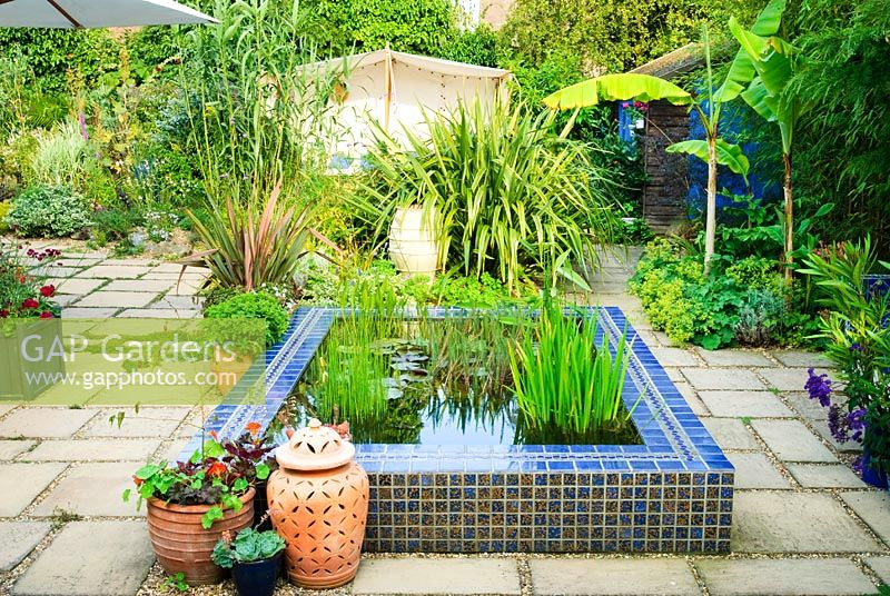 Paved courtyard with raised pool clad in blue glazed tiles. View to Moroccan style outdoor tent. Phormiums, Musa 'Basjoo', Bamboo, Arundo donax in borders. Decorative terracotta planters and containers