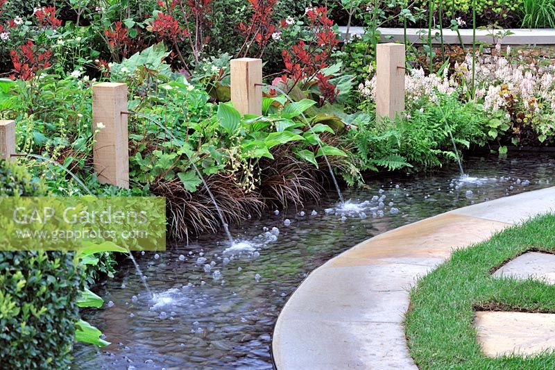 Circular rill with copper water spouts fixed in timber pillars - RHS Malvern Spring Gardening Show