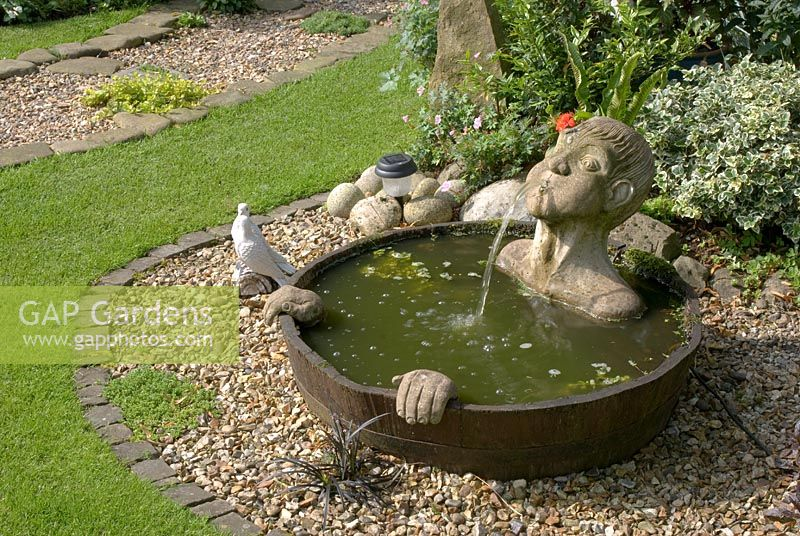 Gap Gardens A Half Barrel Water Feature With Submerged Head Water Spout And Hands Sunk In