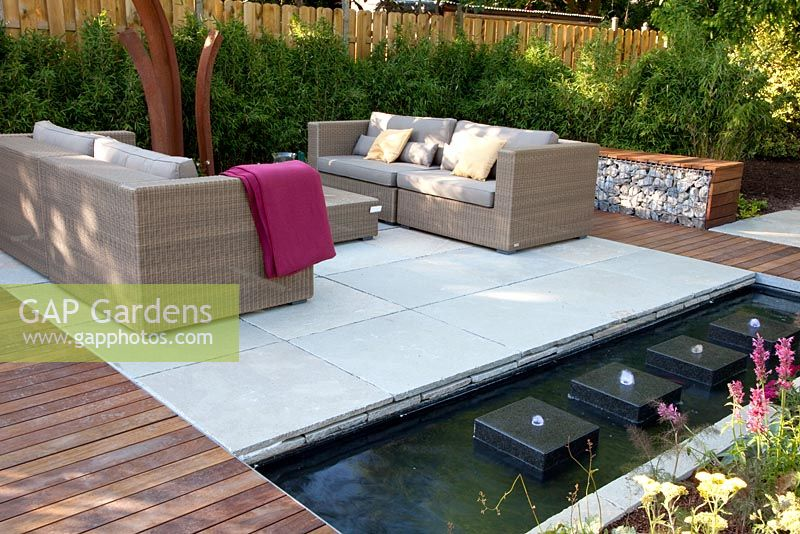 Gap gardens small garden with wicker sofas on decked and for Square pond ideas