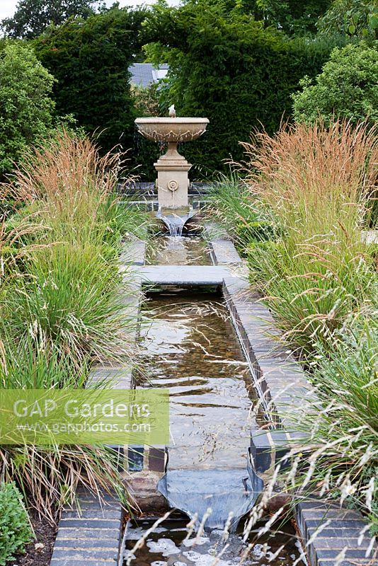 Gap Gardens Long Rectangular Pond And Fountain With Calamagrostis Grass Surrounding It