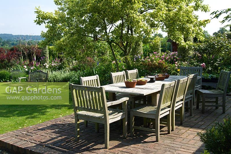 Wooden table and chairs in country garden. Sandhill Farm House, Hampshire, in June.