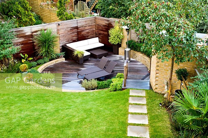 Overview of small urban garden in September with contemporary furniture and patio heater on circular sunken decked terrace. Raised bed and planting of Phormium, Arbutus unedo tree and Lavandula. Paving slab path across lawn. Muswell Hill, London