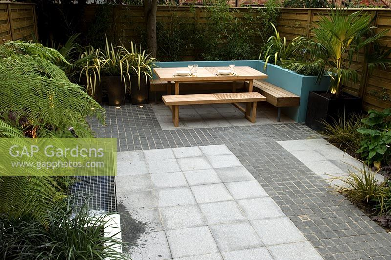 Small Urban Garden With Paved Patio And Seating Area, Phormium In Planters