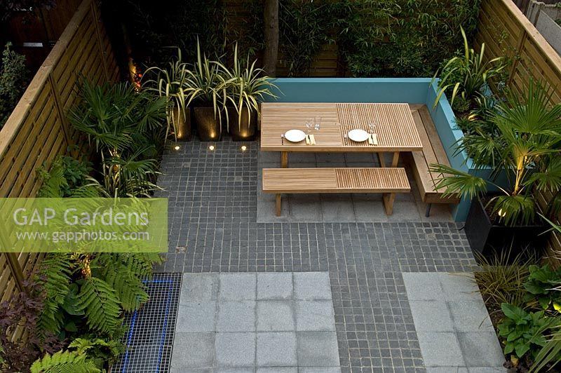 Elevated View Of Small Urban Garden With Paved And Cobblestone Patio And  Built In Seating Area