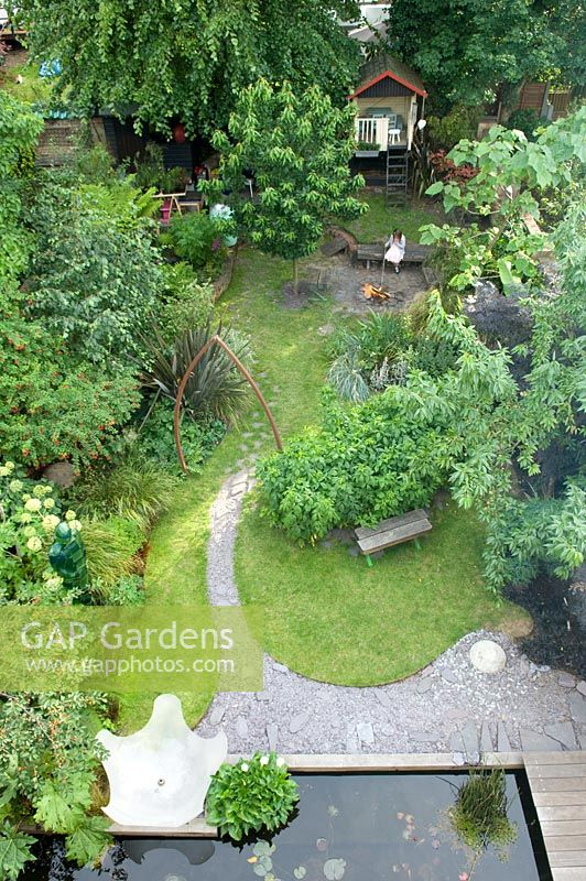 Urban garden viewed from above, showing resin water feature, rectangular pond and curved slate path under metal arch. Yulia Badian garden, London, UK