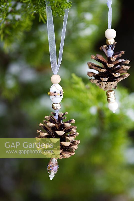Making pine cone decorations with beads - Finished decoration hanging in a snow covered conifer tree.