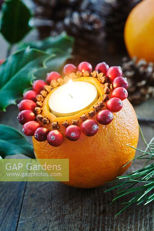 Making an orange, cranberry and clove tealight decoration - Finished decoration with a lit tealight.