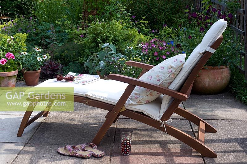 Reclining steamer chair with cushion on terrace overlooking garden border
