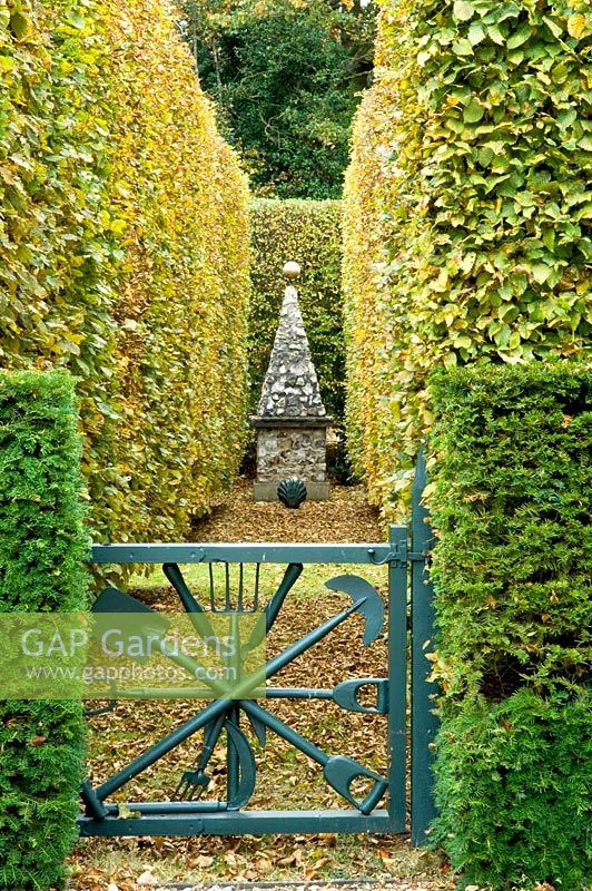 Blue gate leading to clipped Fagus and Taxus baccata hedges and stone obelisk - Silverstone Farm, Norfolk