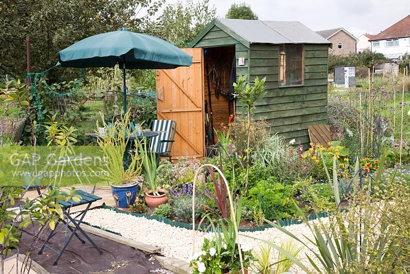 Small shed on allotment with gravel path, mixed planting and seating area