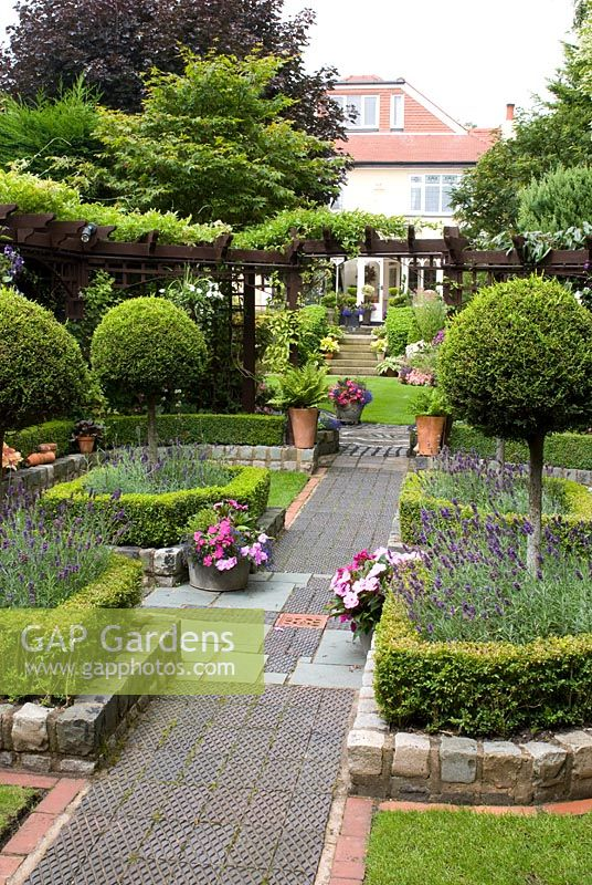 The secluded parterre garden with paths and walls made of small reclaimed cobbles, station platform tiles and bricks, parterre with Buxus sempervirens - Box hedges, Lavandula angustifolia 'Hidcote' and Thuja topiary standards, pergola with Clematis - Brocklebank Road, Southport, Lancashire NGS