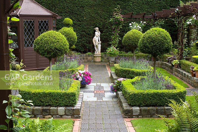 Secluded parterre garden with paths and walls made from reclaimed cobbles, station platform tiles and bricks, parterre with Buxus sempervirens - Box hedges, Lavandula angustifolia 'Hidcote' and Thuja topiary standards, pergola, summer house and classical garden statue - Brocklebank Road, Southport, Lancashire NGS
