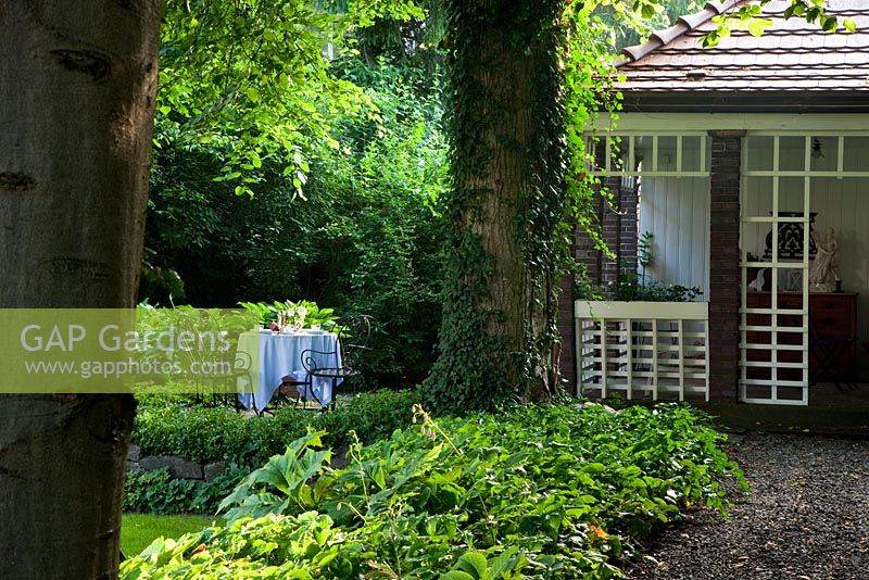 GAP Gardens - A white clothed table on the raised veranda of a brick ...
