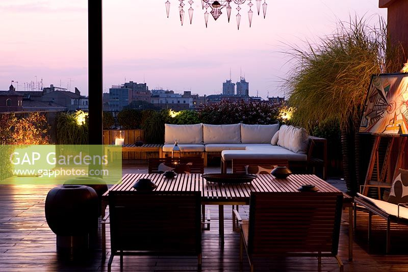 Terrace with contemporary seating area with sofas at night with modern lighting in Ferrara, Italy