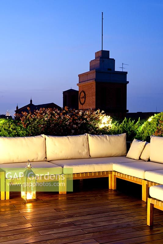 Terrace in Ferrara with sofas with planting 'Abelia compacta', 'Ilex Crenata' and Trachelospermum jasminoides' at dusk with lighting
