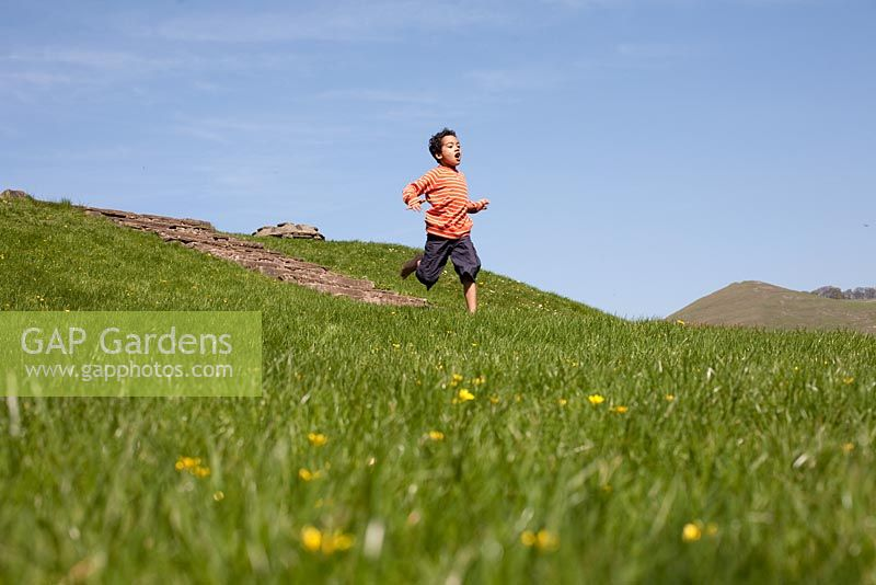 Boy running down a hill