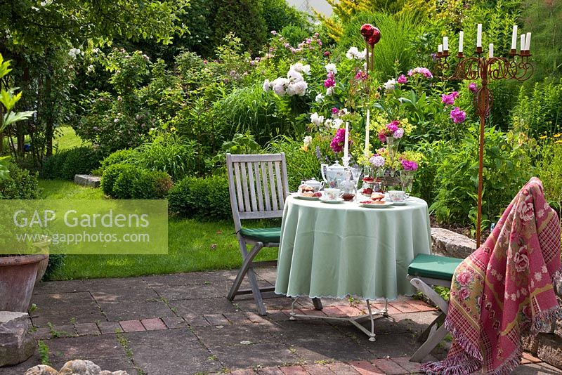 Patio with table set for meal, wooden chairs, and a rusty metal chandelier next to planting of Buxus, Paeonia and Rosa