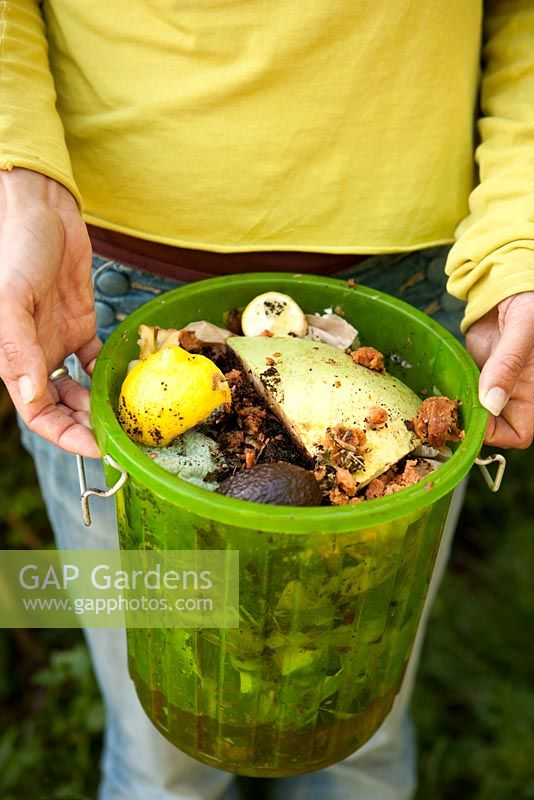 Woman holding bucket full of kitchen food waste ready for composting