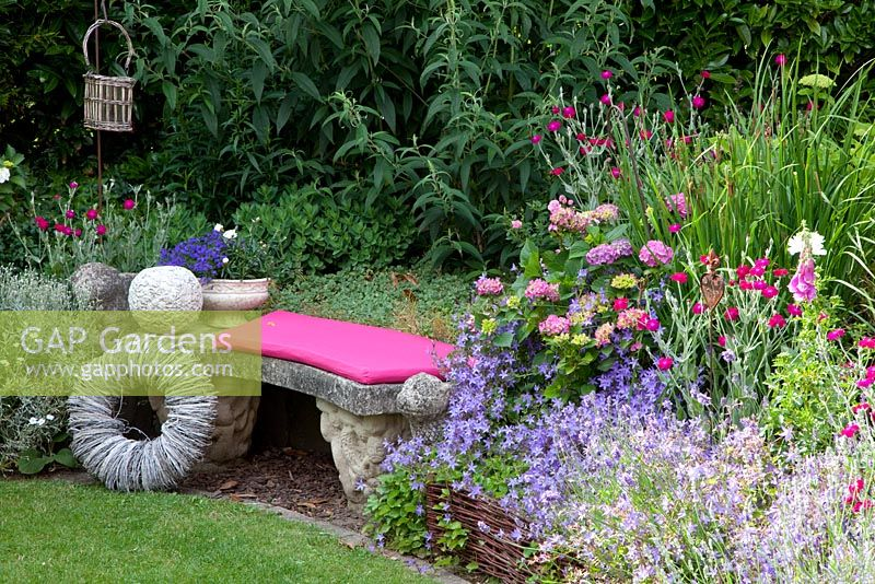 Stone bench with willow decorations next to border of  Hydrangea, Campanula poscharskyana and Lavandula - Lavender - Scheper Town Garden