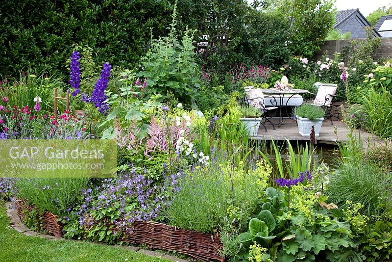 Small Town Garden With Seating Area Next To Pond. Border With Woven Willow  Edging