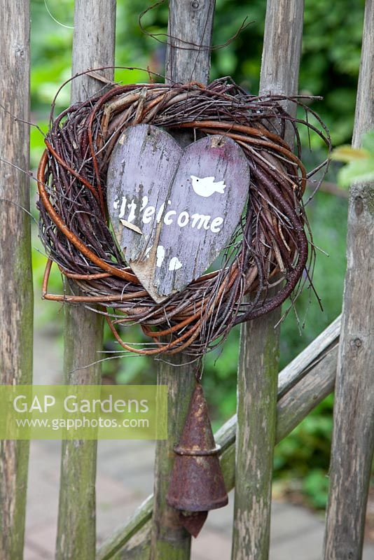 Rustic 'Welcome' sign and rusty bell on wooden gate - Scheper Town Garden