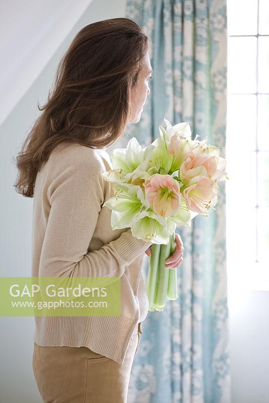 Girl in bathroom holding a vase filled with Amaryllis - Hippeastrum 'Cherry Blossom' and 'Challenger'
