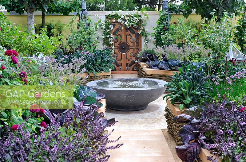 Kitchen garden with water feature and herbs and vegetables planted in raised beds made with Woven willow and cedar wood
