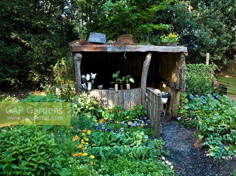Rustic Wooden Shelter In Vegetable Garden