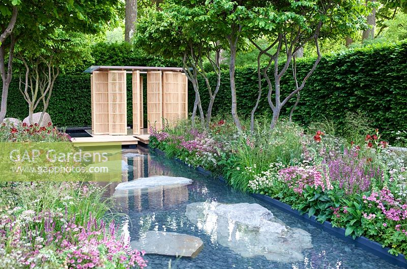 Pond surrounded by pink and purple themed borders with Japanese style pavilion and Parrotia persica - Persian Ironwood trees - The Laurent-Perrier Garden - Nature and Human Intervention - Gold Medal Winner, RHS Chelsea Flower Show 2011