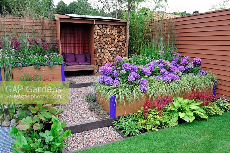 Raised beds in low maintenance garden with solar panels on the roof of reclaimed timber shelter, and raised bed with Hydrangea 'Teller Blue' and Carex 'Evergold' - RHS Tatton Park Flower Show 2011