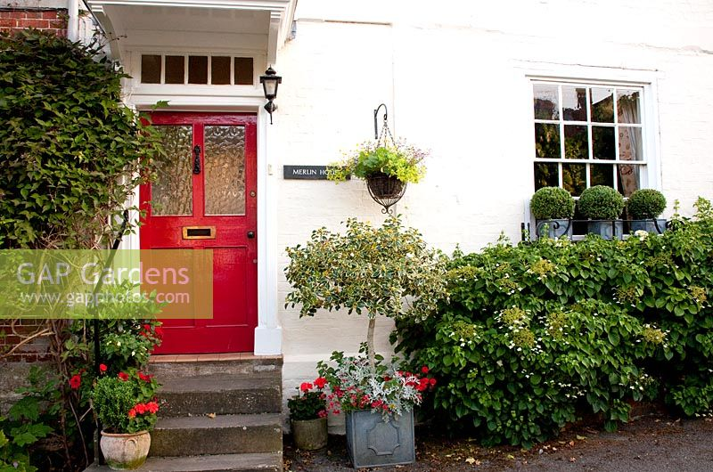 Cottage front garden with colourful pot plants and red front door - Merlin House, Wiltshire, UK