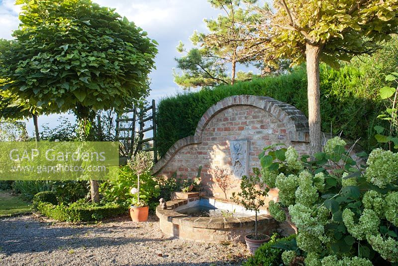 Wall mounted head of Neptune water spout above brick pool, Garden Hackl, Mistelbach Austria