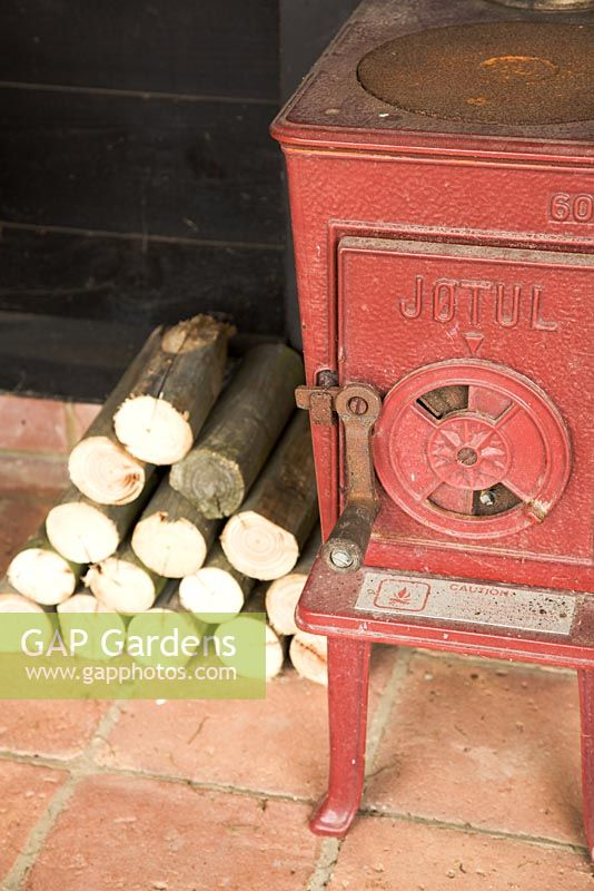 Log burning stove and logs in outhouse