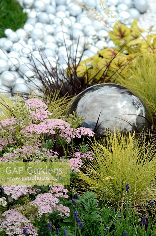 Achillea millefolium 'Lilac Beauty' with Festuca glauca 'Golden Toupee' surrounding a reflecting sphere feature