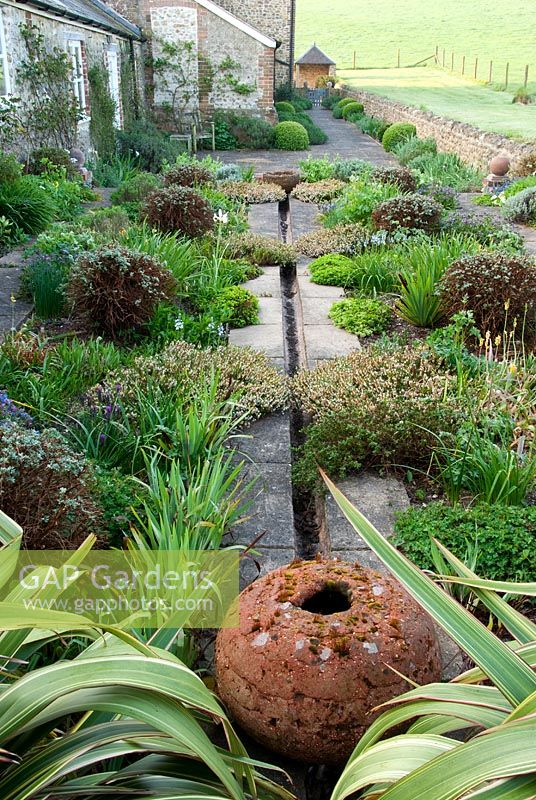 Rill garden behind farmhouse with terracotta spheres and plants including Phormium tenax, Potentilla fruticosa 'Primrose Beauty', Erica carnea 'Springwood White', Dorset
