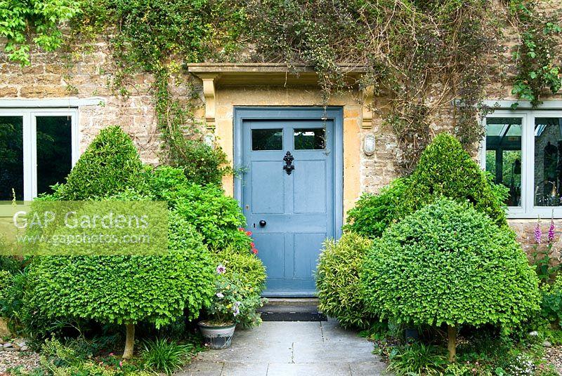 gap gardens front door framed by clipped evergreens. Black Bedroom Furniture Sets. Home Design Ideas