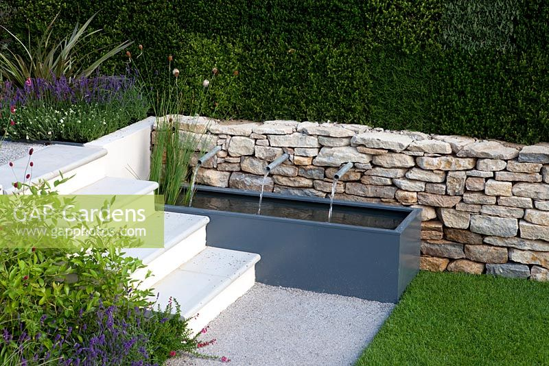 Trough Water Feature With Spouts In Modern Garden