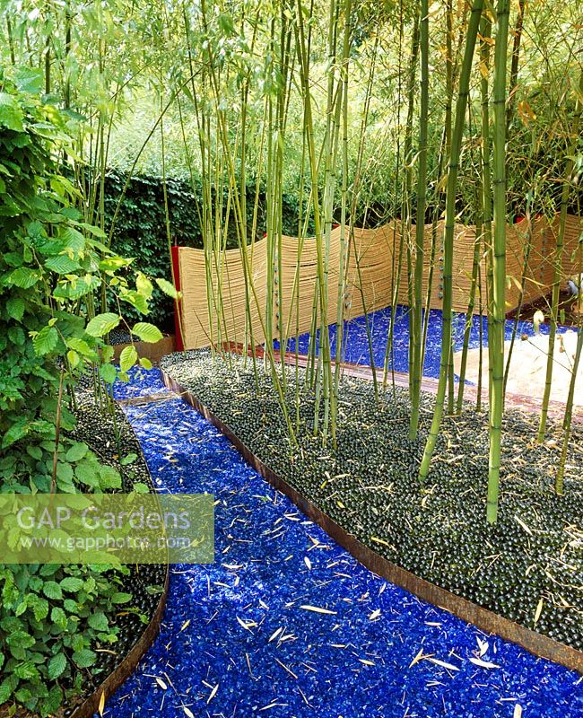 Glass garden - Blue glass and green marbles act as mulch beneath bamboos with rope fencing