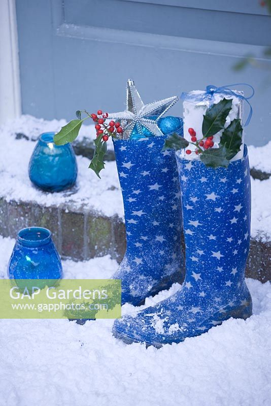 Candles on door step with blue boots and Holly sprigs