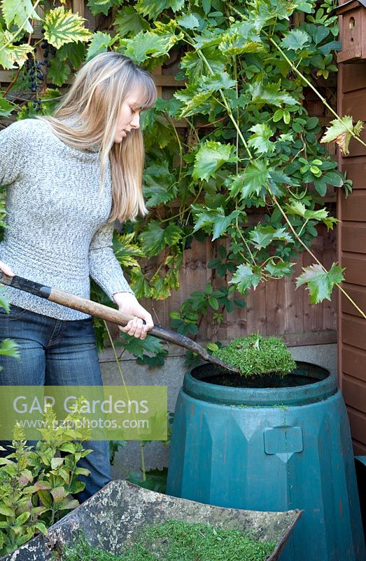 Woman filling compost bin with lawn cuttings