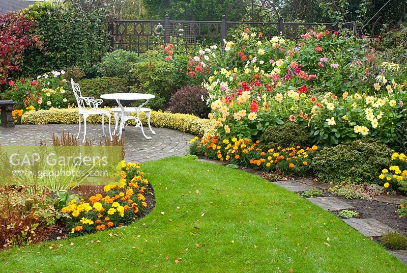 Late summer garden with path leading to circular cobble sett patio and seating, and colourful mixed borders with Azalea, Astilbe and summer bedding Dahlia and Tagetes