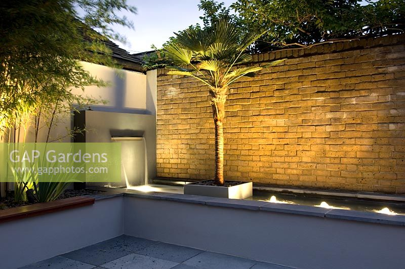 Small urban garden with water feature and uplighters, London