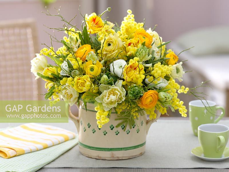 Yellow and white scented bouquet with Tulipa - tulips, Ranunculus - buttercups, Acacia - mimosa, Hyacinthus - Hyacinths and branches of Vaccinium - blueberry
