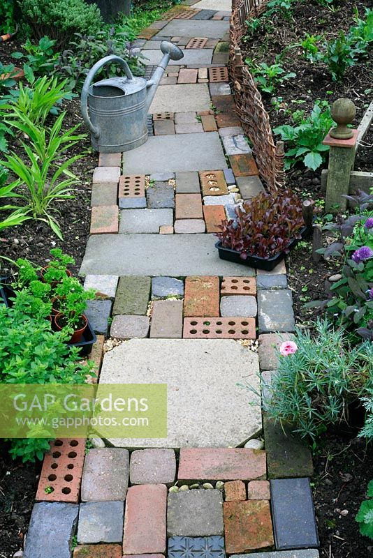 Cottage garden style path made with salvaged materials including slabs, bricks, concrete block pavers and pebbles