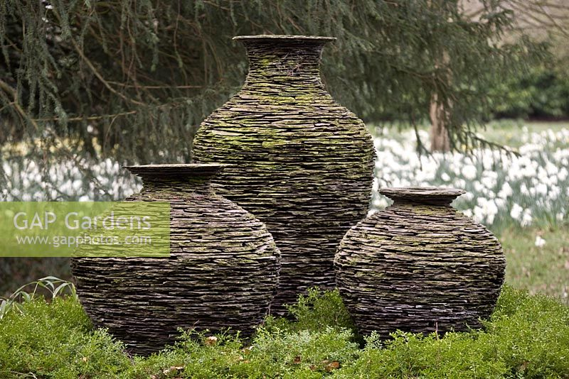 Pots made of Welsh slate and created to look like stone walls. The pots are in the meadow, Highgrove Garden, March 2008.