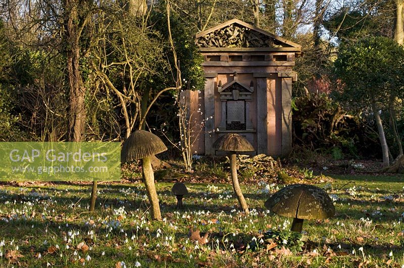 Wooden toadstool sculpture and green oak temple with snow drops in the Stumpery, February 2011.
