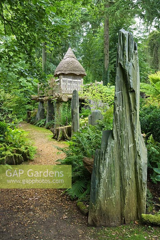 The thatched tree house 'Hollyrood House' in the Stumpery has a rustic platform made of oak and is supported by shards of Welsh slate. Highgrove Garden, August 2007.