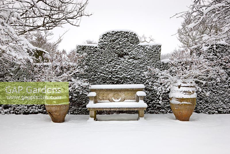 Stone bench and two pots covered in snow, Highgrove Garden, January 2010.